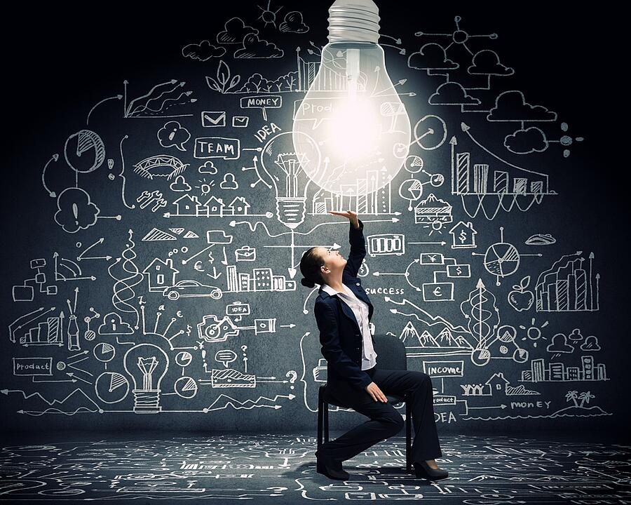 young-businesswoman-sitting-on-chair-with-big-light-bulb-above